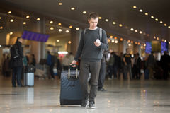 Young traveler using mobile phone in airport Stock Image