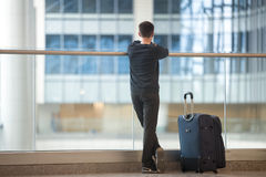 Young traveler waiting for airplane. Young handsome man in 20s waiting for flight, standing in modern airport terminal, travelling with luggage bag, wearing Stock Image