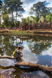 Young traveler wearing a hat with backpack and tripod - at Angkor Wat Stock Image