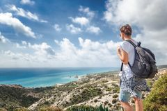 A young traveler woman with a backpack on a stunning landscape b. Ackground with the sea and green hills, traveling, hiking, together with nature, freedom and Royalty Free Stock Image