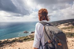 A young traveler woman with a backpack on a stunning landscape b. Ackground with the sea and green hills, traveling, hiking, together with nature, freedom and Stock Image
