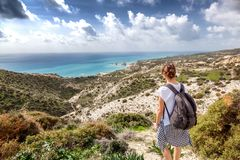 A young traveler woman with a backpack on a stunning landscape b. Ackground with the sea and green hills, traveling, hiking, together with nature, freedom and Royalty Free Stock Photography