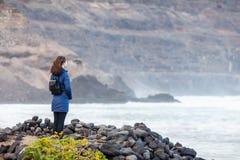 Young traveler woman enjoy ocean on black volcanic beach in Lanz stock photo