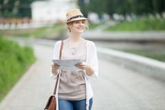 Young traveler woman in straw hat walking with map on the trip Royalty Free Stock Photo