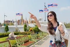 Young traveler woman visiting Bangkok Grand Palace. Young pretty traveler woman visiting Bangkok Grand Palace and pointing beautiful building view sharing with Stock Photography