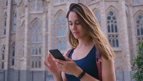 Young traveler girl walking in the city and using smartphone, attractive woman traveling at Barcelona, Spain, slow. Young traveler woman walking in the city and stock video