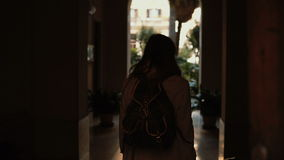 Young traveler woman walking with a suitcase in the street. Girl opens the door and comes into an arch. stock video footage