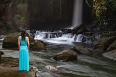 Young traveler woman at waterfall in tropical forest, Ubud, Bali. Sumampan waterfall. View from back. Slow shutter speed, motion stock image