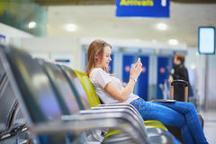 Young travelerin international airport checking her mobile phone while waiting for her flight Stock Image
