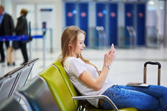 Young travelerin international airport checking her mobile phone while waiting for her flight Stock Photos