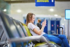 Young travelerin international airport checking her mobile phone while waiting for her flight Royalty Free Stock Image