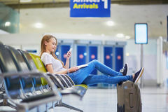 Young travelerin international airport checking her mobile phone while waiting for her flight. Young traveler with carry on luggage in international airport royalty free stock photography