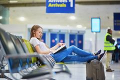 Young travelerin international airport reading a book while waiting for her flight. Young traveler with carry on luggage in international airport reading a book royalty free stock photography