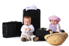 Young Travelers. Two babies with their boarding pass, surrounded by suitcases.  The boy has his shoes in his hands.  Isolated on white Stock Photography