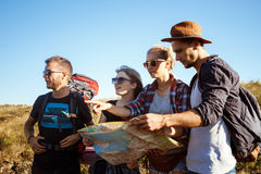 Young travelers with backpacks smiling, looking for route on map. Stock Images