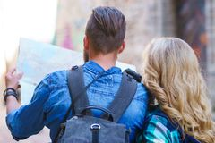Young travelers with a tourist map. Man and woman having vacation. Backpackers, traveling and tourism concept. royalty free stock photo