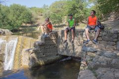 Young Travelers, hikers sits near a waterfall royalty free stock image