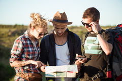 Young travelers looking for route on map, walking in canyon. Stock Photography