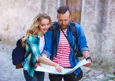 Young travelers with a tourist map. Man and woman having vacation. Backpackers, traveling and tourism concept. stock image