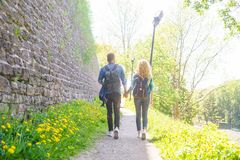 Young travelers walking in a park. Man and woman having vacation. Backpackers, traveling and tourism. Young travelers walking in a park. Man and woman having stock image