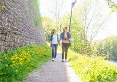 Young travelers walking in a park. Man and woman having vacation. Backpackers, traveling and tourism. Young travelers walking in a park. Man and woman having royalty free stock image