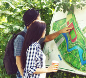 Young traveling couple: checking a map in a park. Royalty Free Stock Photo