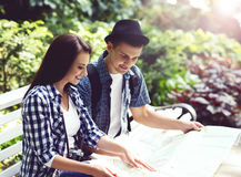 Young traveling couple checking out the map in the park. Stock Photos