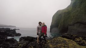 Young traveling couple in raincoats standing on the shore of the sea and enjoying the trip. Tourists man and woman. Young traveling couple in raincoats standing stock footage