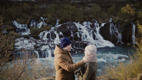 Young traveling couple on a romantic date near the waterfalls in Iceland. Man and woman hugging on nature. Young traveling couple on a romantic date in stock footage