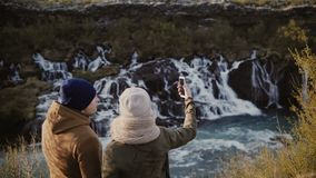 Young traveling couple standing in mountains valley near waterfall and talking pictures or selfie photos on smartphone. Young traveling couple standing in stock video