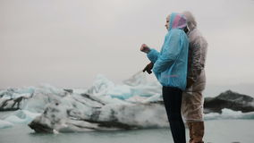 Young traveling couple wearing raincoats enjoying the view in ice lagoon in Iceland. Tourists on the nature at cold day. Young traveling couple wearing stock video