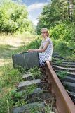 Young traveling girl sitting on rail Royalty Free Stock Images