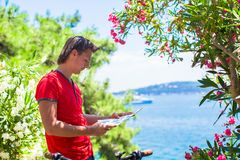 Young traveling man with map while exploring Royalty Free Stock Images