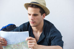 Young traveling man reading map. Portrait of a young traveling man reading map Stock Photo
