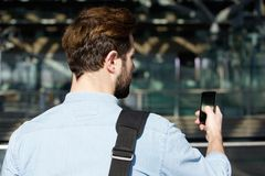 Young traveling man reading text message on mobile phone Stock Photography