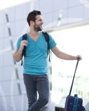 Young traveling man standing outside with bag. Portrait of a cheerful young traveling man standing outside with bag Stock Image