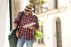 Young traveling man walking with map and bag. Portrait of a young traveling man walking with map and bag Royalty Free Stock Photos