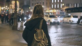 Young traveling woman with backpack crossing the traffic road, tourist looking around and find the way in the evening. Stylish female exploring the new city stock video