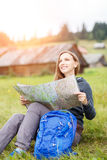 Young traveling woman with backpack looking in map Royalty Free Stock Photo