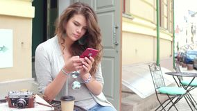Young traveling woman with curly hair typing sms on smartphone. Street cafe, tourist girl drinking coffee, communicating on phone stock video