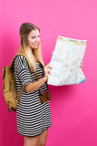 Young traveling woman holding a map. On a pink background Stock Photos
