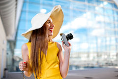 Young traveling woman with photo camera and panama dressed in ye. Llow dress standing in front of the airport or high-tech background and looking toward Stock Photo