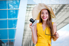 Young traveling woman with photo camera and panama dressed in ye Royalty Free Stock Images