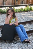 Young woman sitting with suitcase  Stock Image