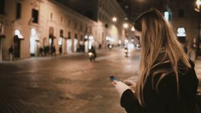 Young traveling woman walking in the city centre in evening and using the smartphone, try to find the way and go away. stock video footage