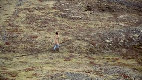 Young traveling woman walking in mountain valley alone in windy day. Female exploring new place and thinking. stock video