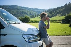 Young traveller enjoys cup of coffee next to van royalty free stock photography