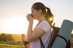 Travelling hiking backpacking sunset success inspiration. Young traveller feel relax and drinking tea from the metallic tourists cup outdoor on the sunset Royalty Free Stock Image