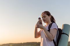 Travelling hiking backpacking sunset success inspiration. Young traveller going to drink coffee from the metallic tourists cup outdoor on the sunset. Concept of Stock Image