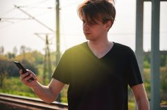 Young traveller man talking through the phone at the railway station during hot summer weather, making gestures while talking stock photography
